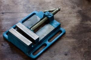Blauer Maschinenschraubstock auf braunem Holztisch.