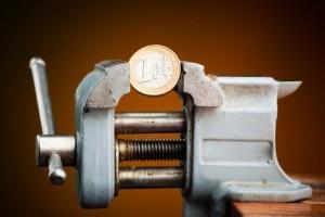 Schraubstock mit 1 Euro Münze zwischen den backen als Symbol für Schraubstock Angebote
