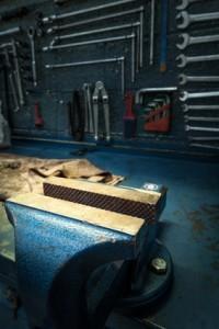 Blauer Schraubstock mit geöffneten Backen auf Werkbank montiert.