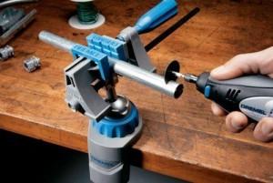 Dremel Multi Schraubstock mit eingespanntem Rohr, das gerade zugesägt wird.